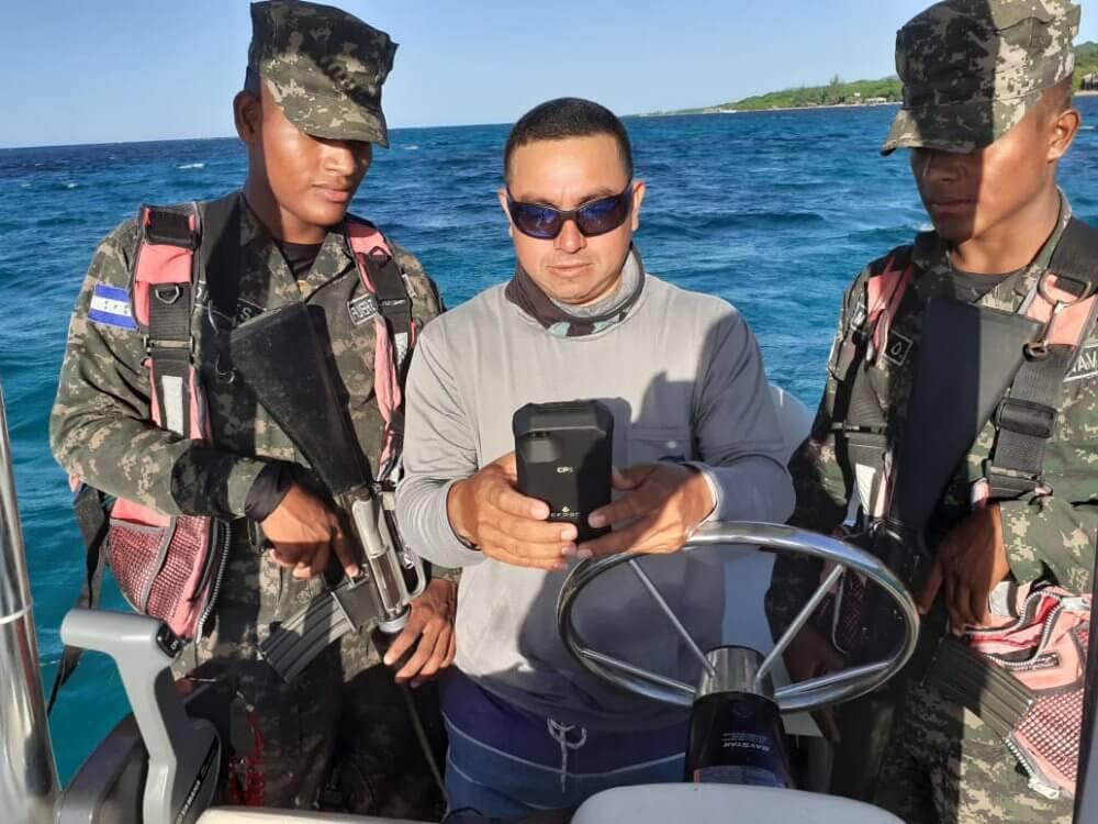 A Roatan Marine Park ranger and members of the Honduran Navy patrol the coastline with the CP3.
