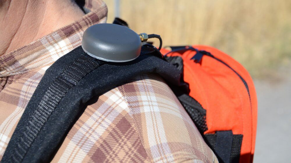 An external antenna from Juniper Systems attached to a backpack shoulder strap.